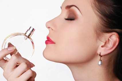 Beautiful young woman smelling her perfume